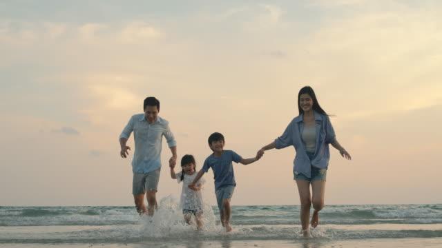アジアの家族は幸せな感情と夏休みに海を実行しています。スローモーション。家族、休日、旅行のコンセプト。 - 母娘 笑顔 日本人点の映像素材/bロール