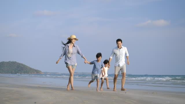 アジアの家族は一緒にビーチで幸せな感情で実行しています。スローモーション。家族、休日、旅行のコンセプト。 - 息子点の映像素材/bロール
