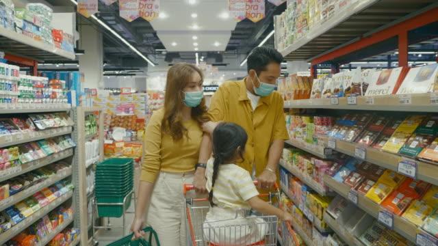vídeos y material grabado en eventos de stock de la familia asiática compra en un supermercado local. - snack aisle