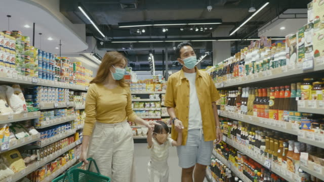 Asian family shopping at a local supermarket. Young asian family shopping for groceries together with daughter at their local supermarket. snack aisle stock videos & royalty-free footage
