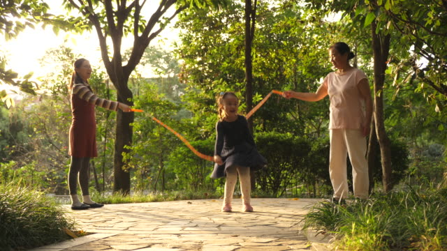 Asian family skipping rope outdoor in the park