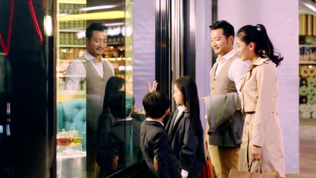 asian family standing in front of a shop window in shopping mall happy asian family with two children standing in front of and looking through shop window in shopping mall department store stock videos & royalty-free footage