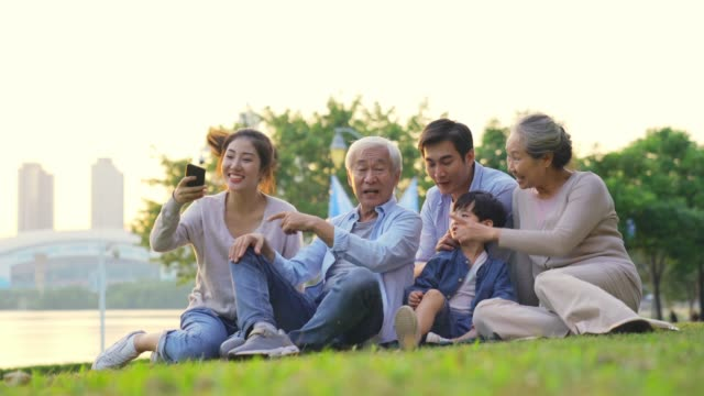 asian family taking a selfie outdoors in park