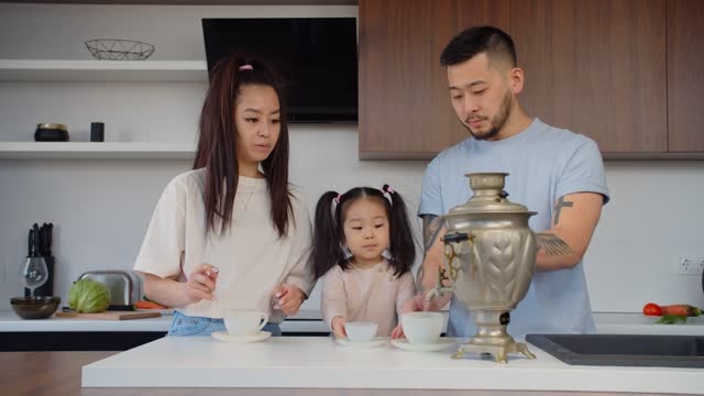 Asian family tea drinking at home using vintage samovar