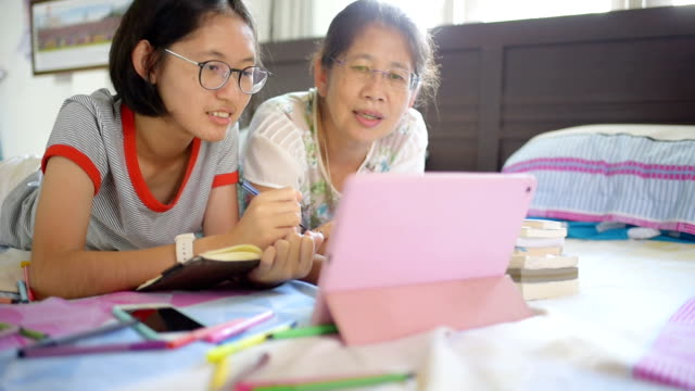 Asian family using digital tablet and smart phone do their work at home and relax with online shopping video