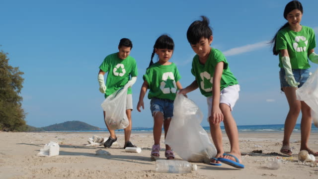 Asian family volunteer member cleaning summer beach and keeping garbage together in cleaning day. Concept of waste environment, recycle, ecology, pollution and volunteer. 4k resolution. Asian family volunteer member cleaning summer beach and keeping garbage together in cleaning day. Concept of waste environment, recycle, ecology, pollution and volunteer. 4k resolution. ecosystem stock videos & royalty-free footage