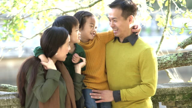 Asian family with two children at the park video