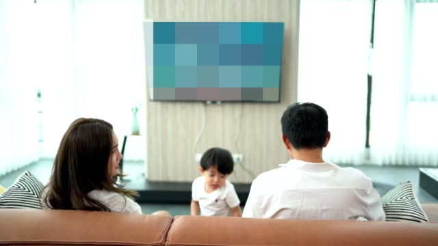 Asian family with two children watching tv and gaming , Fun on the weekend