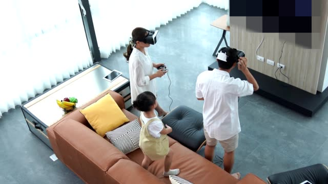 Asian family with two children watching tv and gaming