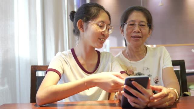 自宅で宿題を行うためのデジタルタブレットとスマートフォンを使用してリラックスして休暇にアジアの家族の若い十代と母親は、ソーシャルネットワーク上のオンラインゲームやテキスト� - オンラインショッピング点の映像素材/bロール