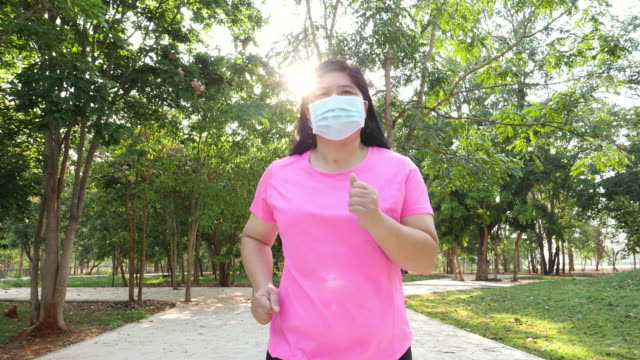asian fat woman beautiful face morning exercise running in the park wear a mask to prevent virus infection through the respiratory system, sunlight up in the background - естественные парковые насаждения стоковые видео и кадры b-roll
