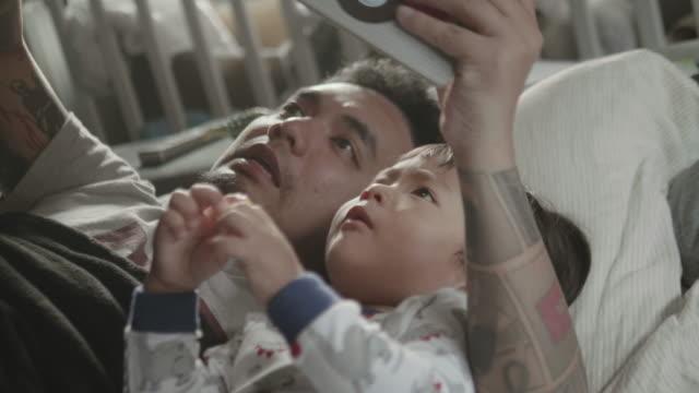 asiatischen vater und kind, ein buch zu lesen, vor dem schlafengehen. - storytelling videos stock-videos und b-roll-filmmaterial