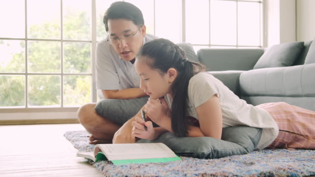 asian father and daughter lying together on the floor and read a book. - two students together asian video stock e b–roll