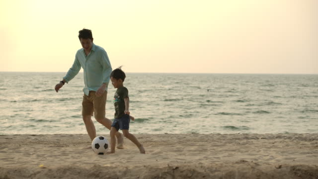 Asian Father and son playing together with ball in football on the beach under sunset background. Slow motion. Happy family concept.