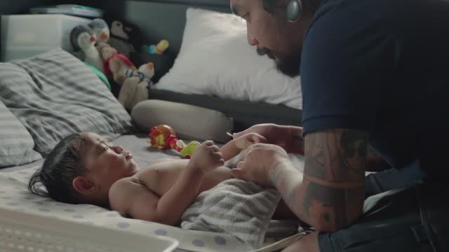 Asiático padre cambiarse de ropa a su bebé en la cama - vídeo