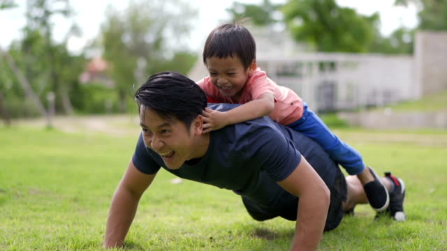 slo mo asian father doing push ups with little boy on his back, outdoors. - termine sportivo video stock e b–roll