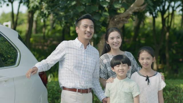 アジアの父母・娘の横に付いている車から彼の息子を保持しています。 - 車点の映像素材/bロール