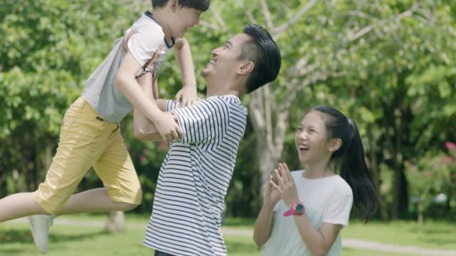 asiatiska far håller upp sin son i luften med dotter bredvid i park i slow motion - kinesiskt ursprung bildbanksvideor och videomaterial från bakom kulisserna