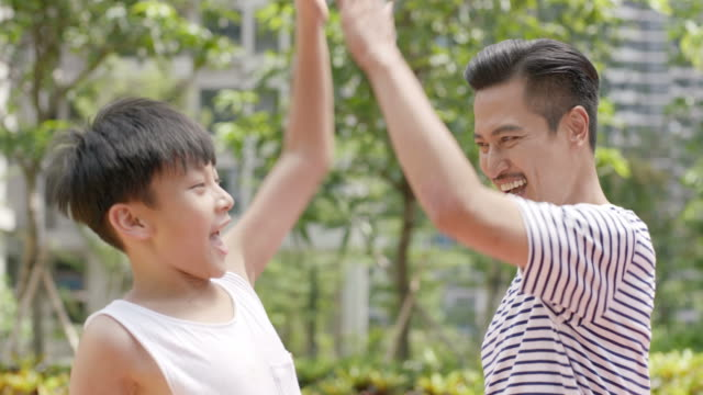 Asian father & son cheering after score during basketball exercising outdoor in the morning video