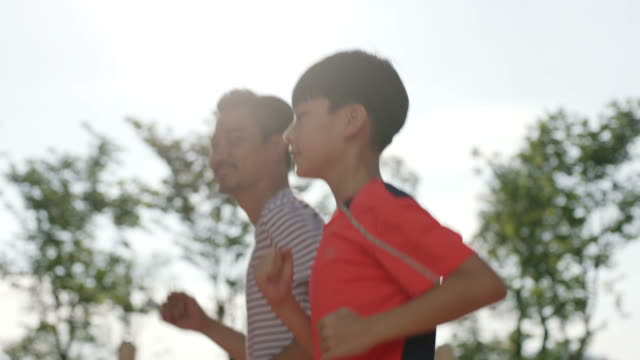 asiatischen vater & sohn joggen am morgen im garten hinten beleuchtet - rennen körperliche aktivität stock-videos und b-roll-filmmaterial