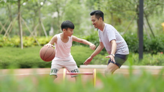 Asian father & son playing basketball in garden in the morning in slow motion video