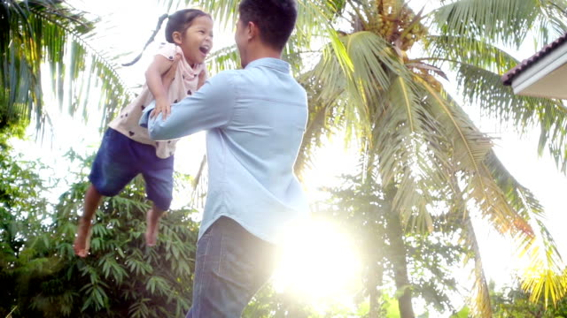 Asian father spinning with happiness daughter around in garden, Slow motion shot in light nature video