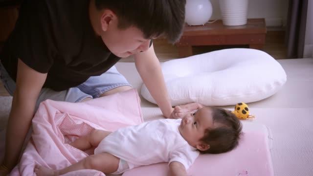 asiatiska far pratar med sin lilla dotter, på den rosa sängen hemma, vit kudde och gul leksak - cosy pillows mother child bildbanksvideor och videomaterial från bakom kulisserna