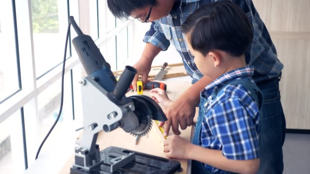 Asian father teach son about wood working or carpenter.