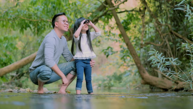 Asian father teaching little girl about sustainability in the forest and excited little girl on a camping trip with binoculars looking for adventures in nature green forest.Teaching Children about Sustainability,Family,Learning,Vacations - vídeo