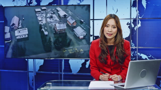 LD Asian female anchor presenting breaking news on floods Wide locked down shot of an Asian female anchor presenting breaking news on floods and helicopter footage of the flooded area is seen on the screen in the background. Shot in Slovenia. journalist stock videos & royalty-free footage