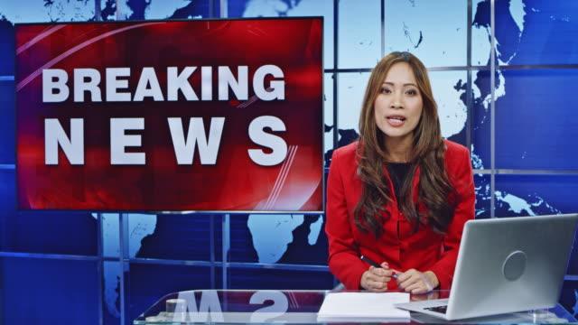 LD Asian female anchor presenting breaking news