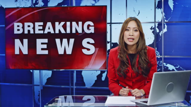 LD Asian female anchor presenting breaking news Wide locked down shot of an Asian female news anchor presenting breaking news. Shot in Slovenia. journalist stock videos & royalty-free footage