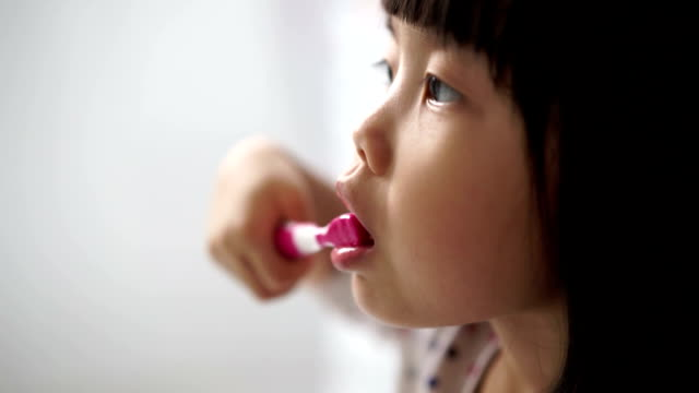 Asian female child enjoying her tooth brushing routine video