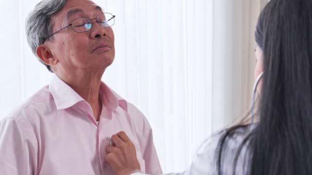 アジアの女性医師が診察室で患者の心臓シニア男性をチェックし、アジアのシニア男性が医療専門家による健康診断を受ける。 - 心臓点の映像素材/bロール