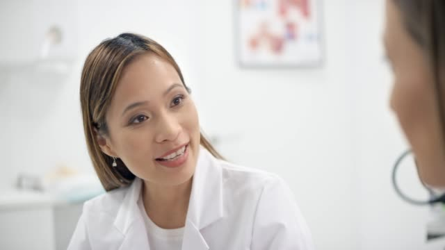 Asian female doctor talking to her patient in her office Medium handheld shot of an Asian female doctor sitting in her office and talking to her female patient. Shot in Slovenia. female doctor stock videos & royalty-free footage