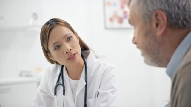 asian female doctor talking to her senior male patient in the office - doctor and patient stock videos & royalty-free footage