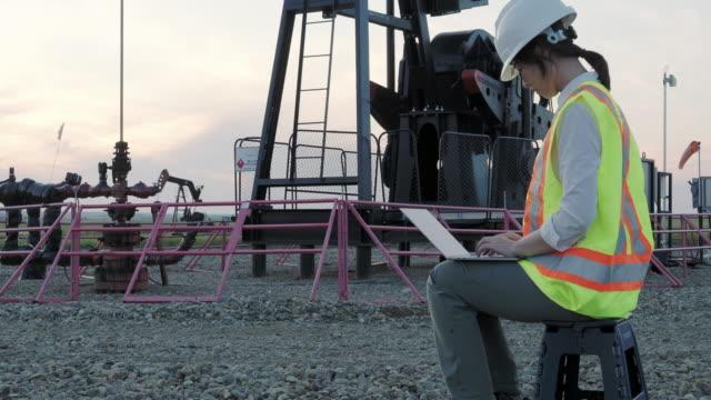 stockvideo's en b-roll-footage met aziatische vrouwelijke ingenieur die aan laptop bij oliegebied werkt - olieraffinaderij