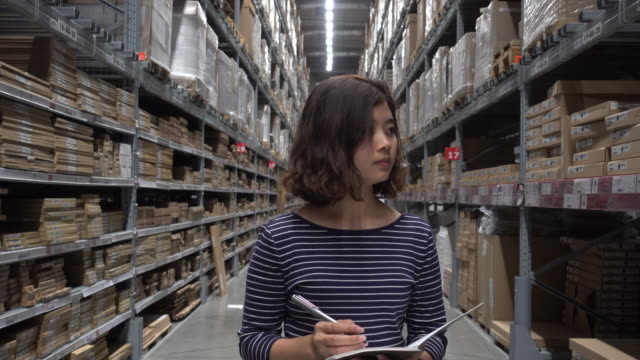 Asian Female factory worker Checking stock in whearhouse