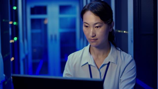 stockvideo's en b-roll-footage met ds aziatische vrouwelijke it engineer controleren van de werking van de server met behulp van haar laptop in de serverruimte - datacenter