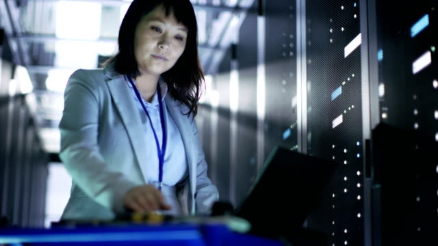 Asian Female IT Engineer Working on a Crash Cart Laptop, She Scans Hard Drives.  She's in Big dataCenter Full of Rack Servers. Asian Female IT Engineer Working on a Crash Cart Laptop, She Scans Hard Drives.  She's in Big dataCenter Full of Rack Servers. Shot on RED EPIC-W 8K Helium Cinema Camera. it professional stock videos & royalty-free footage
