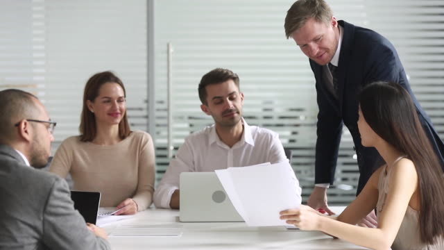 Asian female leader presenting work results at diverse group meeting
