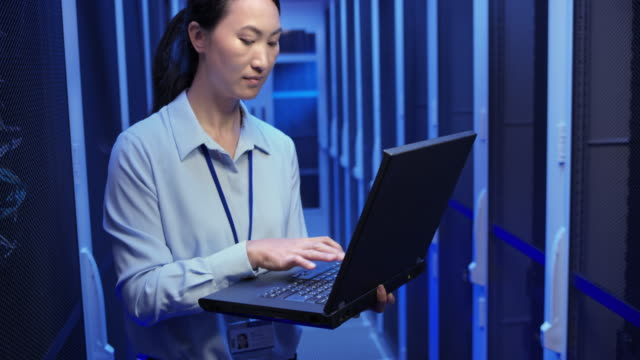 Asian female network engineer doing a system check standing in the server room with his laptop