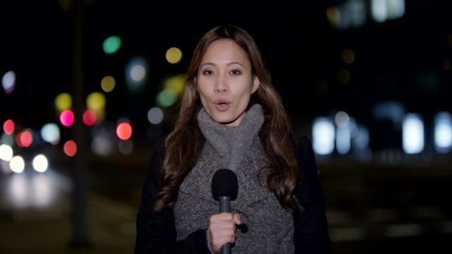 Asian female news reporter reporting live from the city center at night Wide handheld shot of a female Asian on the scene reporter reporting to the studio from the city center at night. Shot in Slovenia. journalist stock videos & royalty-free footage