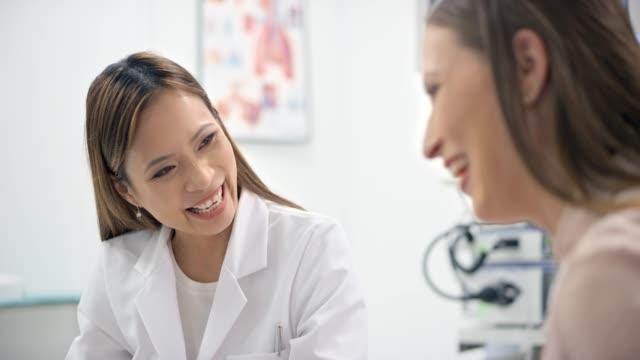 亞洲女性婦科醫生在與懷孕病人交談時微笑, 並在電腦上顯示她的超聲波照片。 - 三四十歲的人 個影片檔及 b 捲影像