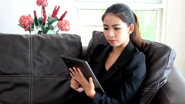 Asian Female Office Worker Using Tablet On Sofa video