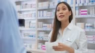istock Asian female pharmacists packing the medicine into a white bag and handing it to the customer 1136014469