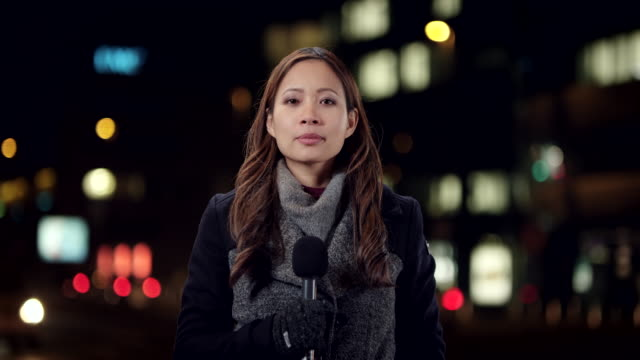Asian female reporter reporting live from the city center at night Wide locked down shot of a female Asian reporter reporting to the studio from the city at night. Shot in Slovenia. journalist stock videos & royalty-free footage