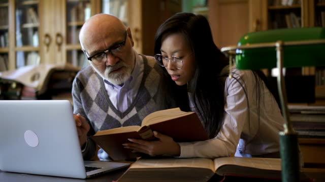 vídeos de stock, filmes e b-roll de assistente de pesquisa feminino asiático trazendo o livro ao professor maduro - college people laptop