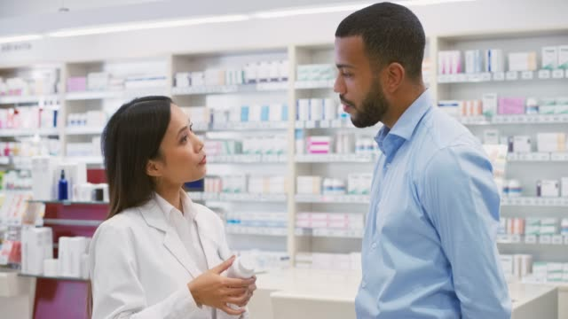 Asian female salesperson at the drugstore advising a young man about a vitamin supplement