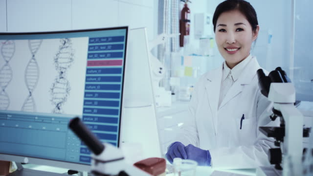 Asian female scientist satisfied with her work. Futuristic Genetic Research Laboratory Female Scientist studying human DNA. Protective workwear. Looking at camera biosensor stock videos & royalty-free footage
